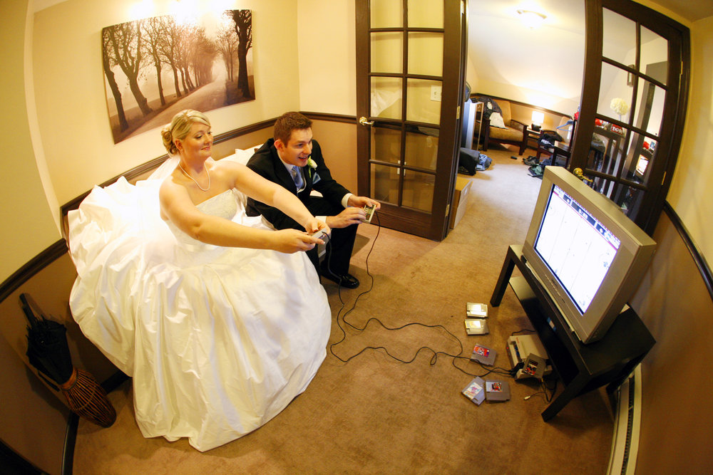 This Is Us - Me and my husband, Reed on our wedding day in 2009. We married on Pi Day. In the small town of Snohomish at the Anthea ballroom. Surrounded by 75 of our closest family and friends. We asked the photographer to get images of our rings on Nintendo controllers and I walked down the aisle to a Final Fantasy theme song. I will forever maintain that our actual wedding date is in 2002 (our first date). SEVEN years before this photo was taken.