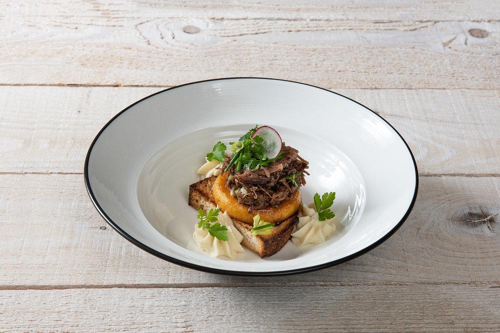 Mickael Jourdan est un véritable artiste. Il tire comme par magie une création à partir de la queue de bœuf, qui honore l'année 2018. Sur un morceau de pain paysan croustillant, il dresse la queue de bœuf effeuillée avec des pommes, du céleri et de la salade craquante pour obtenir une merveilleuse tartine.