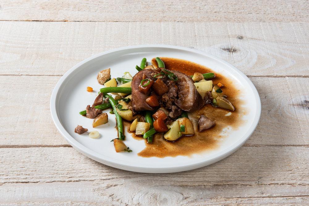 Elia Galliker farcit son groin de porc avec un mélange de chair à saucisse, d'oignons et de carottes en brunoise avant de le faire mijoter précautionneusement. En garniture il sert des haricots et pommes vapeur. Une version innovante du classique Nose-to-Tail.
