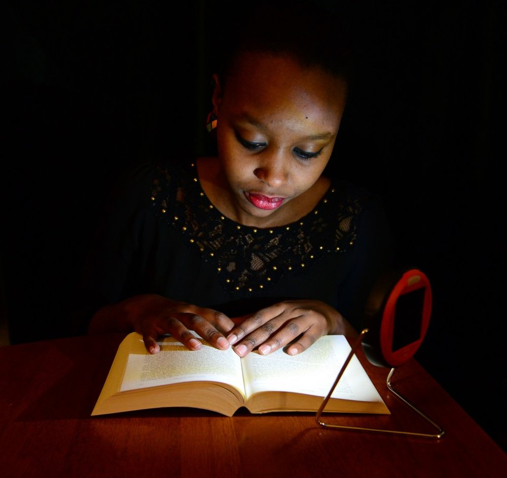 Westminster College student Sandra Nivyabandi, who is from Burundi and Rwanda, demonstrates using one of the solar lamps to be sent to primary students in Rwanda.