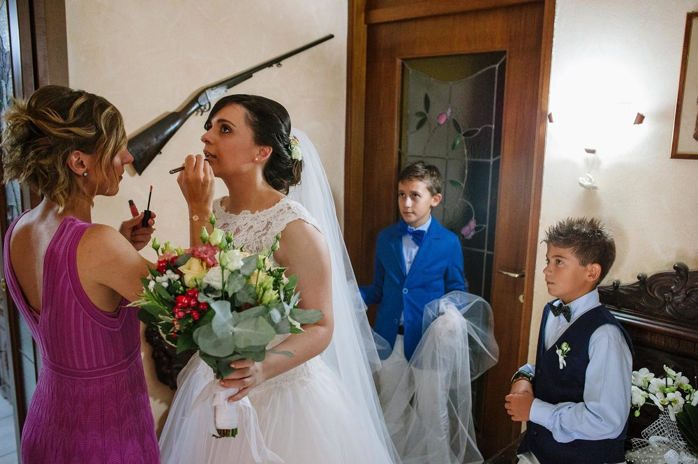 bride-doing-last-make-up-retouches-rifle-on-the-wall-kids-holding-the-veil.jpg