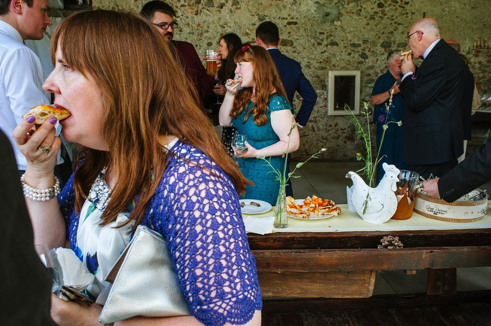 three-guests-at-wedding-eating-pizza-slices-at-the-same-time.jpg
