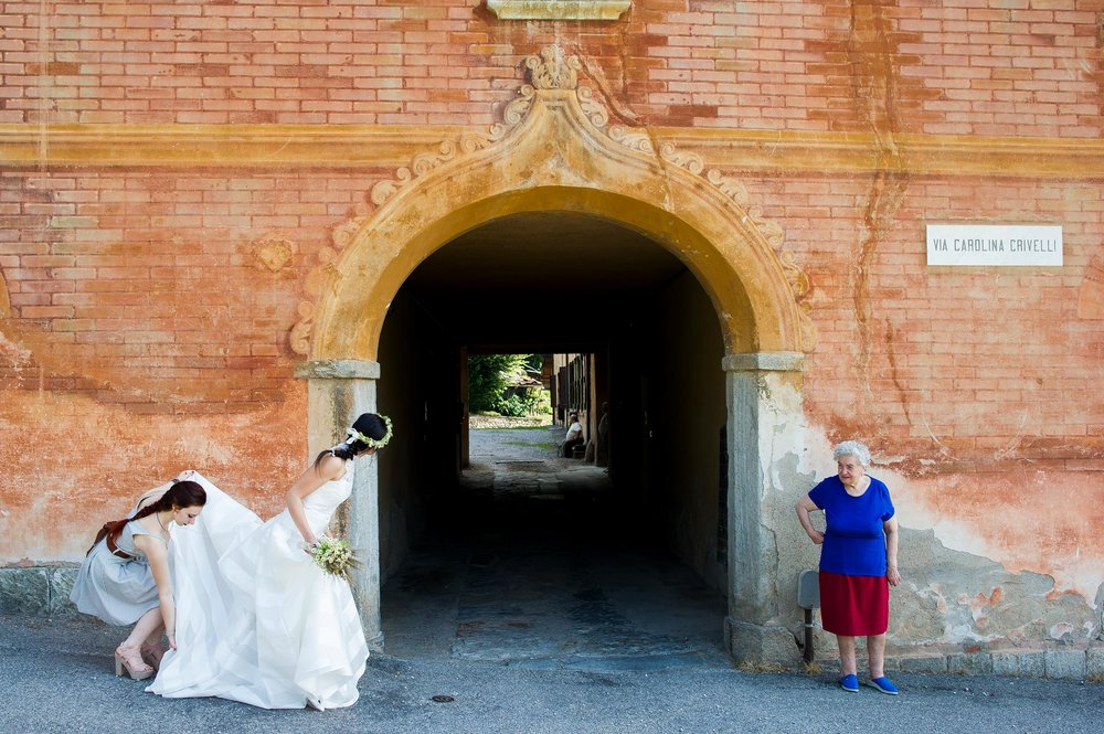 wedding-italy-the-bride-await-for-the-car-while-a-woman-stands-pattern-shapes-colors.jpg