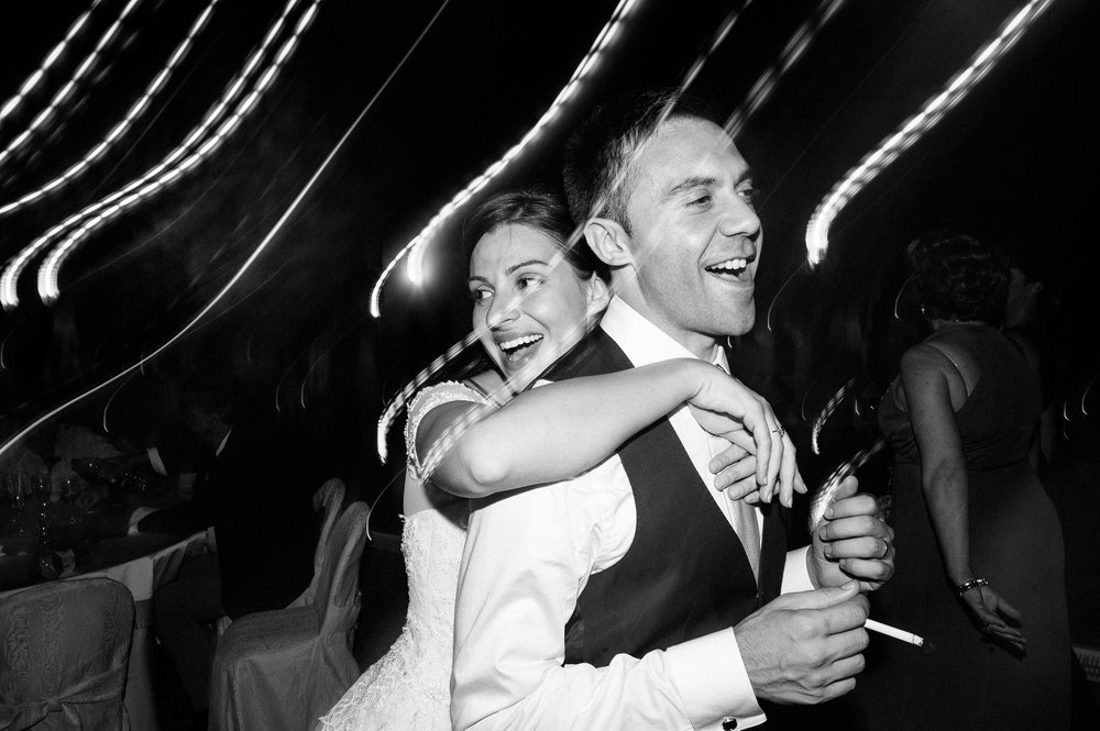 bride-hugs-the-groom-during-wedding-reception-black-and-white-wedding-photography.jpg