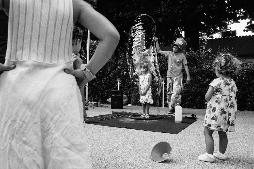 children-watching-a-girl-in-a-tunnel-of-soap-ball-black-and-white-wedding-photography.jpg