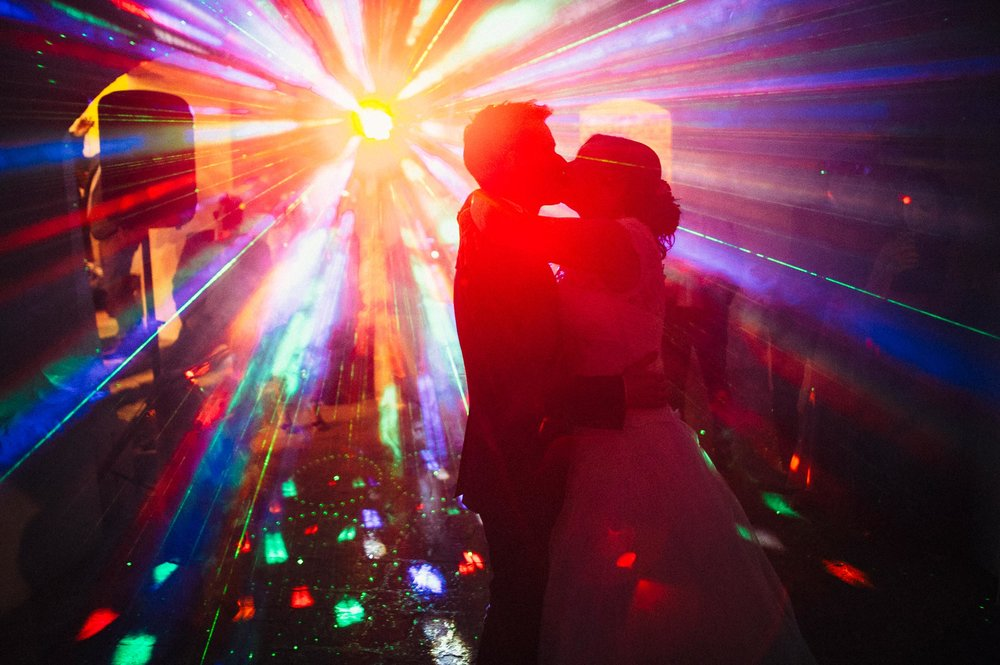 dj-lights-color-flare-strikes-on-the-dancefloor-while-bride-and-groom-kiss-during-the-first-dance-at-wedding.jpg
