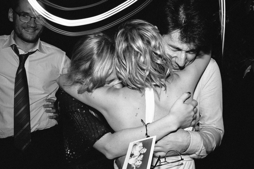 friends-hug-the-bride-after-showing-her-their-polaroid-together-black-and-white-wedding-photography.jpg