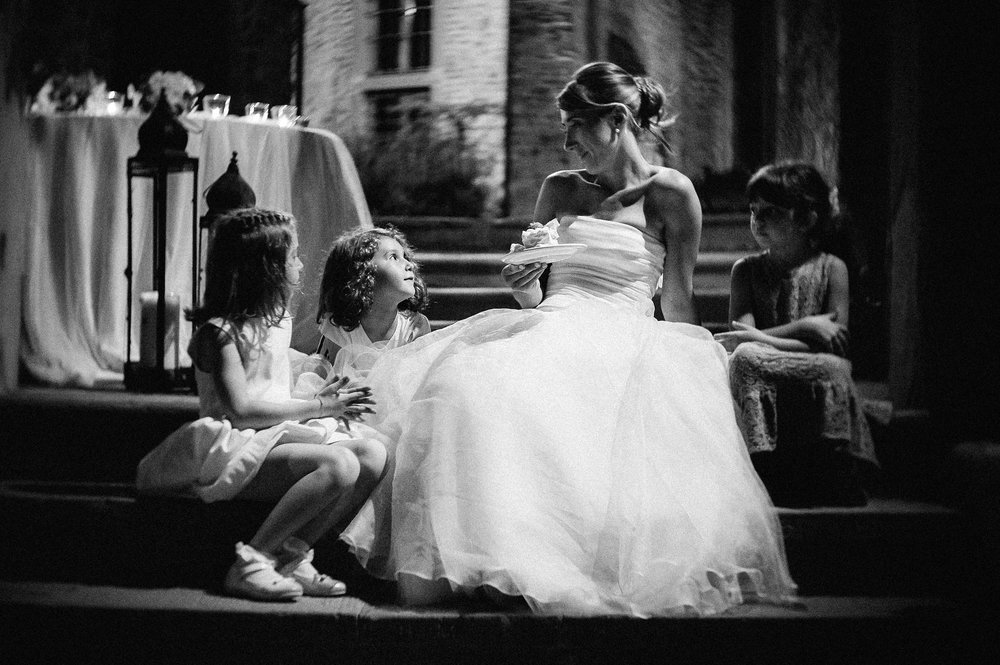 girls-around-the-bride-relaxed-moment-eating-cake-black-and-white-wedding-photography.jpg