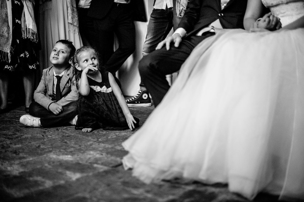 girl-stares-at-the-bride-dreaming-during-short-movi-projection-black-and-white-wedding-photography.jpg