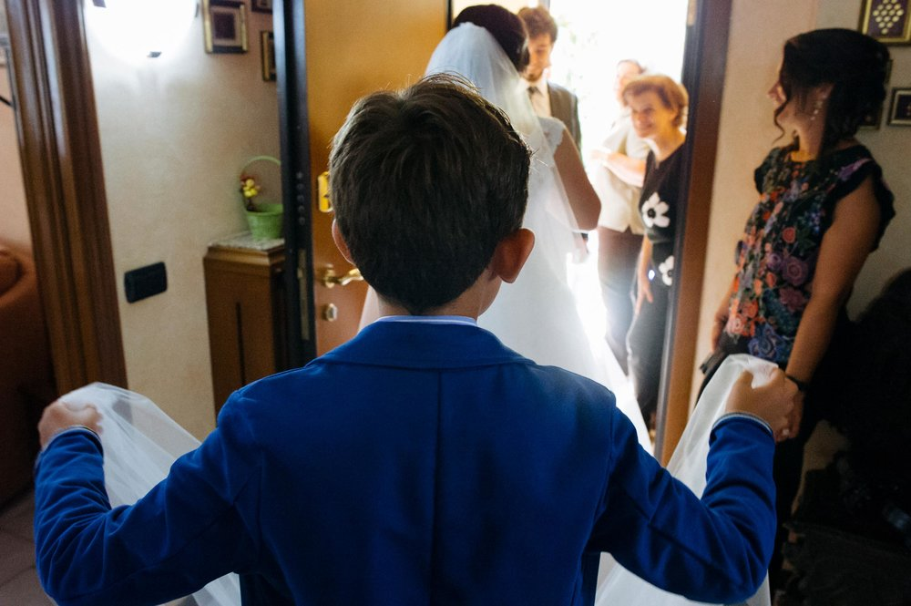 kid-holding-bridal-veil-helping-the-bride-going-out-of-home.jpg
