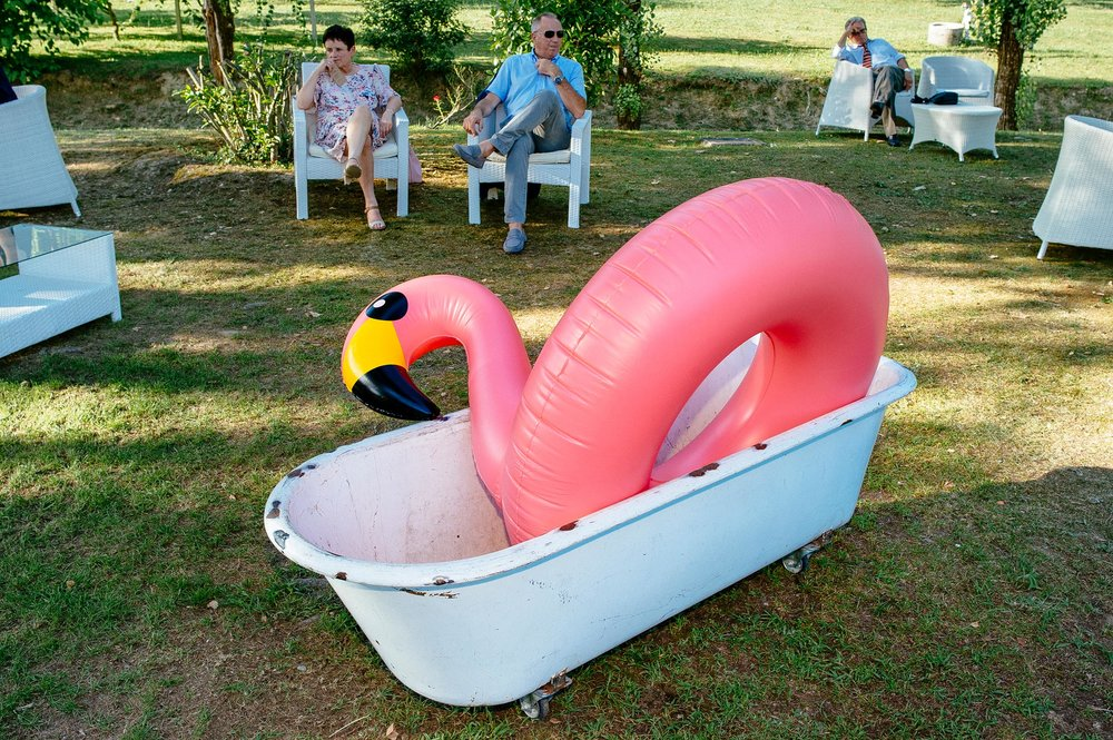 pink-flamingo-sitting-in-a-bathtub-on-the-grass-during-wedding-reception-italy.jpg