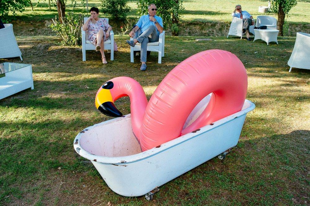 pink-flamingo-sitting-in-a-bathtub-on-the-grass-during-wedding-reception-italy.jpg
