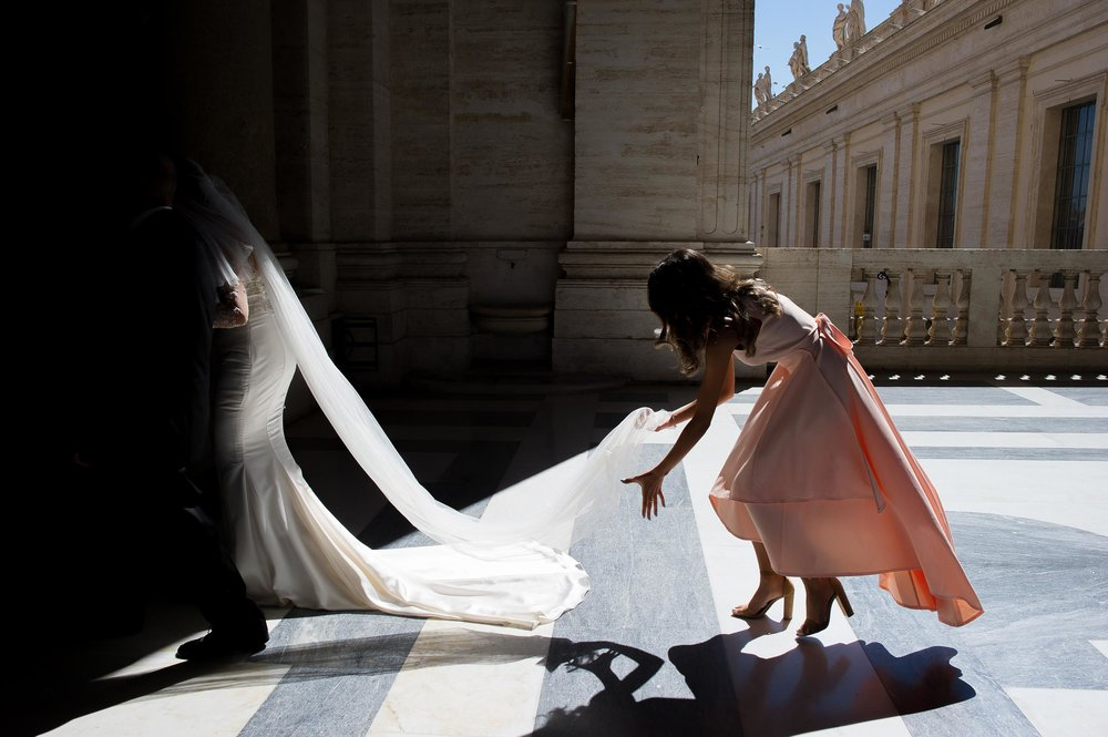 st-peter-basilica-wedding-in-vatican-silhouette-bridesmaid-helps-bride-holding-the-veil.jpg