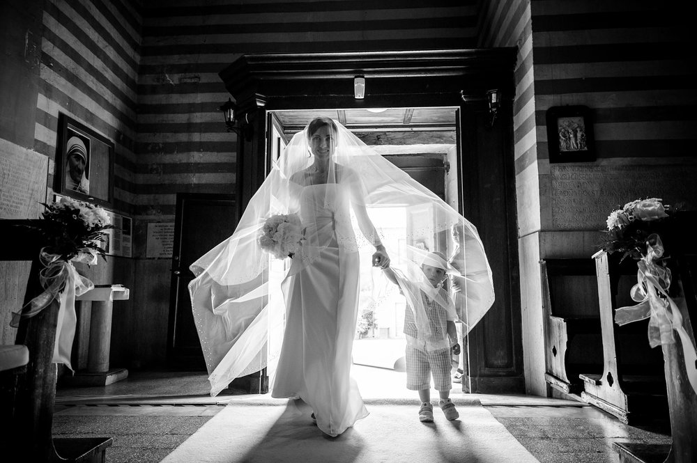 thr-bride-enters-the-church-holding-her-son-by-the-hand-big-bridal-veil-in-italy-black-and-white-wedding-photography.jpg