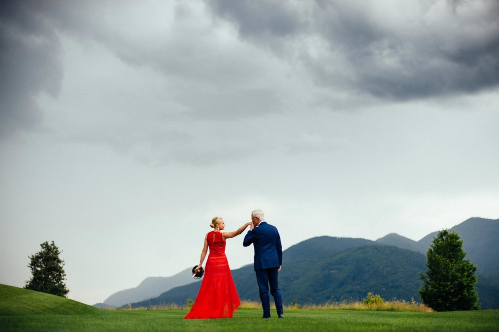 groom-in-blue-kisses-the-bride-with-red-wedding-dress-on-a-green-grass-field-lugano-switzerland.jpg