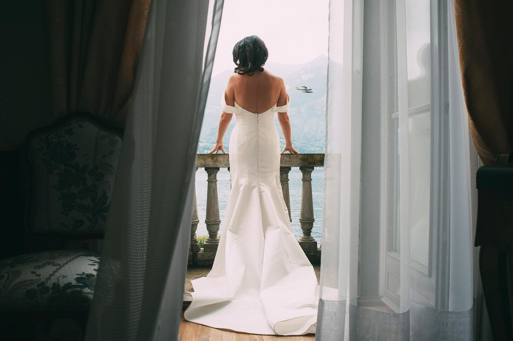 lake-como-bride-on-the-balcony-while-airplane-passes-by-wedding-italy.jpg