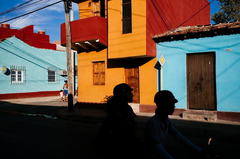 Trinidad-2016-scooter-passes-in-front-of-coloured-houses-while-woman-walks-with-small-daughter-street-photography-by-Alessandro-Avenali.jpg