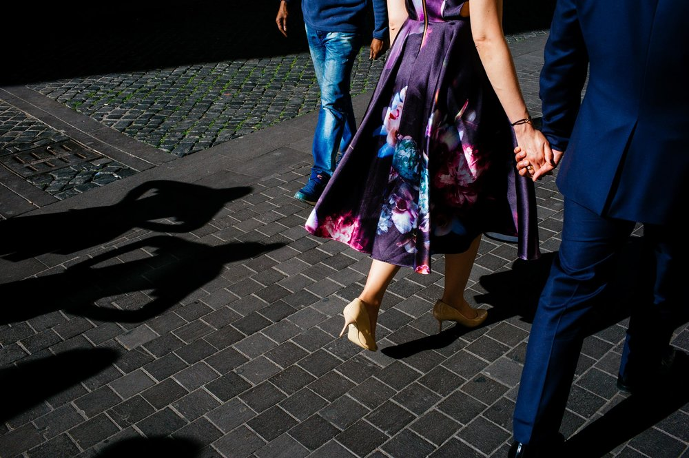 engagement-in-rome-couple-holding-by-the-hands-walking-the-shadow-of-two-passerbies-watching.jpg