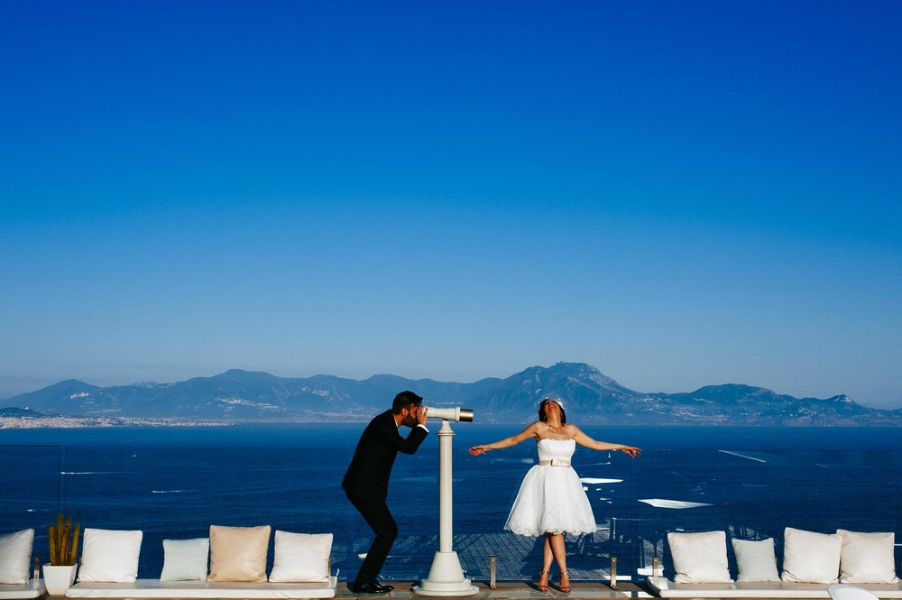 wedding-naples-terrace-over-the-sea-groom-watching-bride-through-spyglass-by-Alessandro-Avenali.jpg