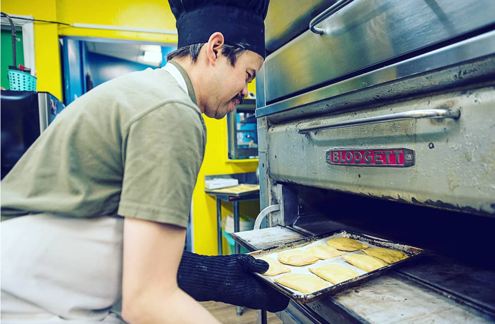 Stefan takes warm, homemade Jamaican patties fresh out of the oven.