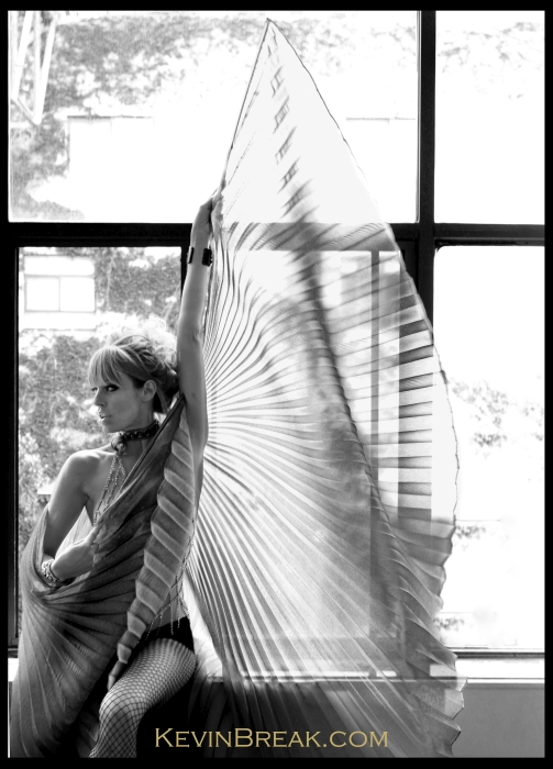 Sexy black and white photo of girl showing high fashion wings in front of huge picture window