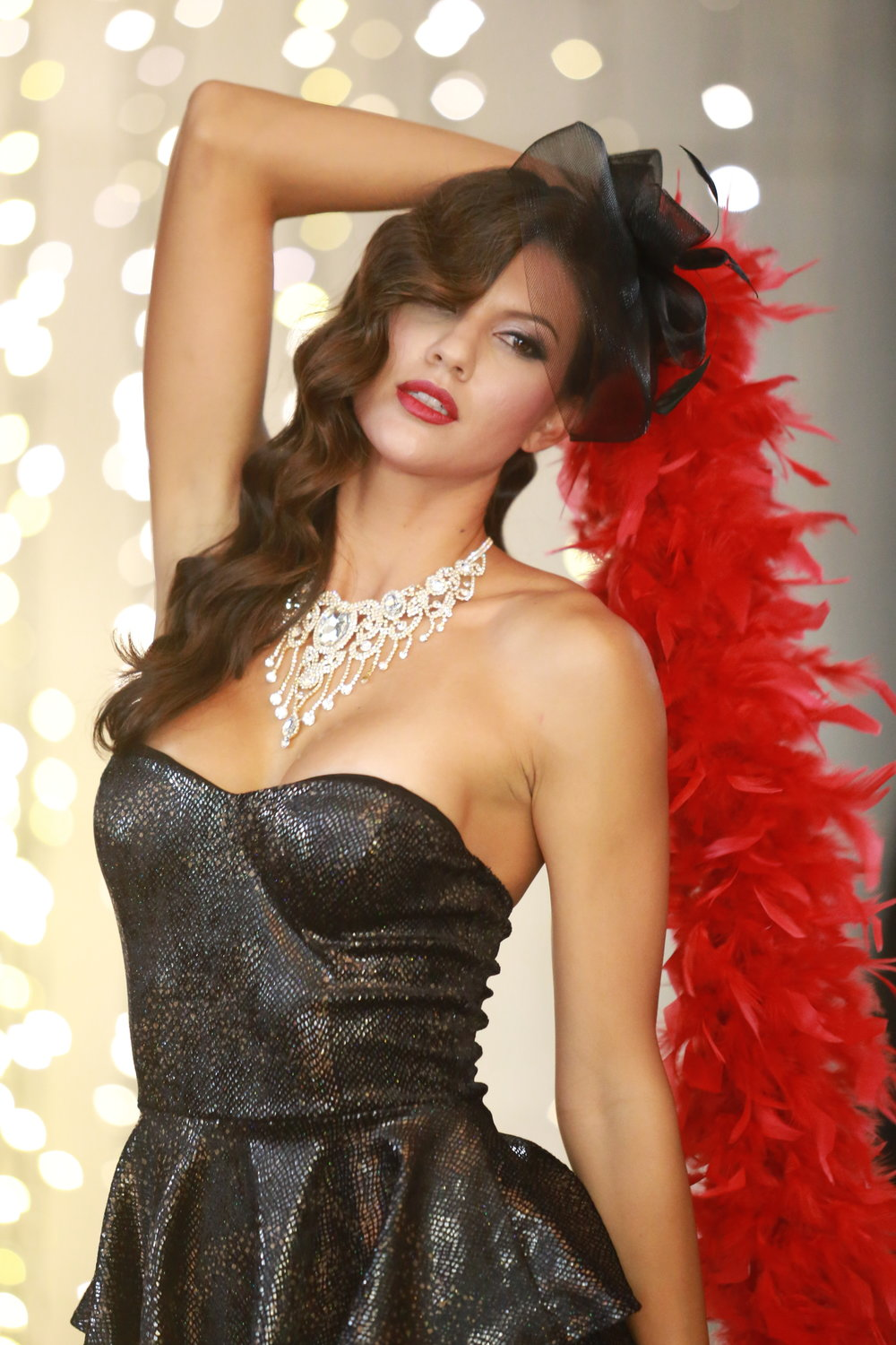 Beautiful model posing with a red feather boa in front of the Star Wall