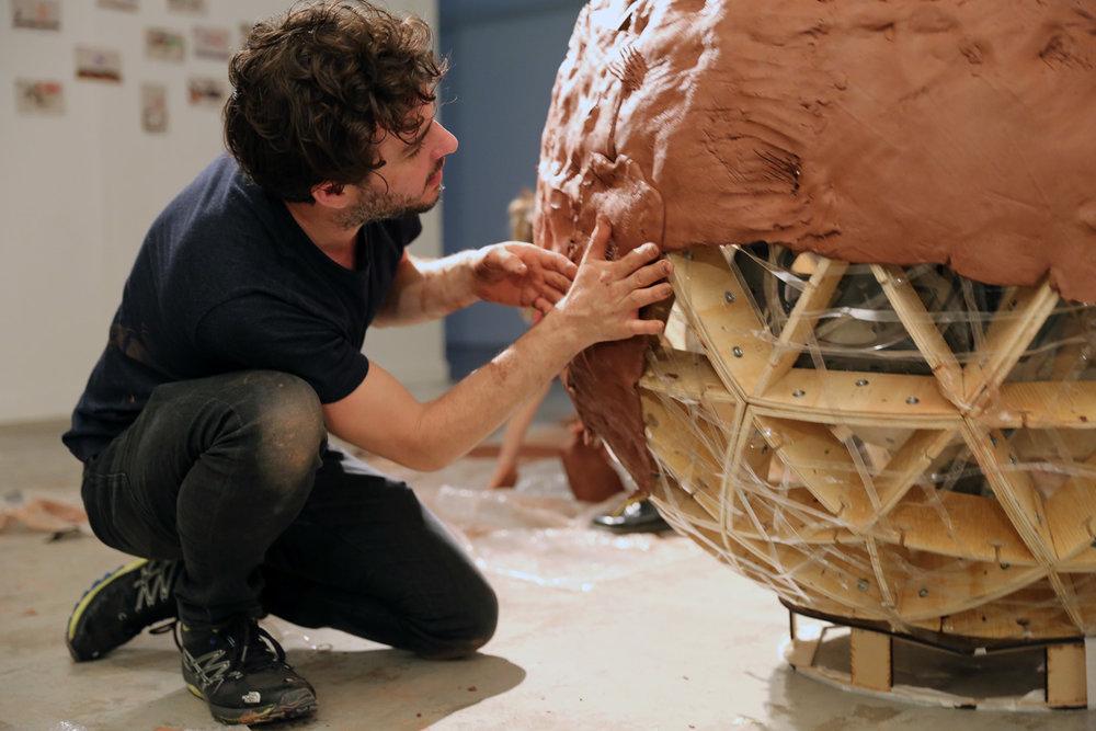 TZ'IJK.3.  UNTREF student hand plastering the robot clay skin.