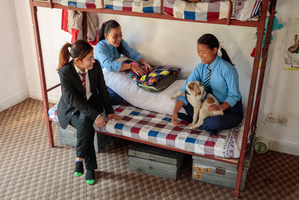 Girls at Hope Home with their pet dog play in their dorm room before leaving for school early in the morning.