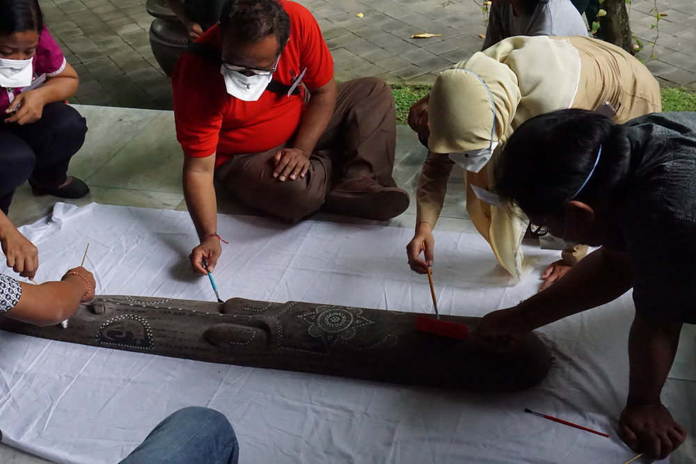 Participants remove ash from timber and stone statues / Photograph by Konservaction
