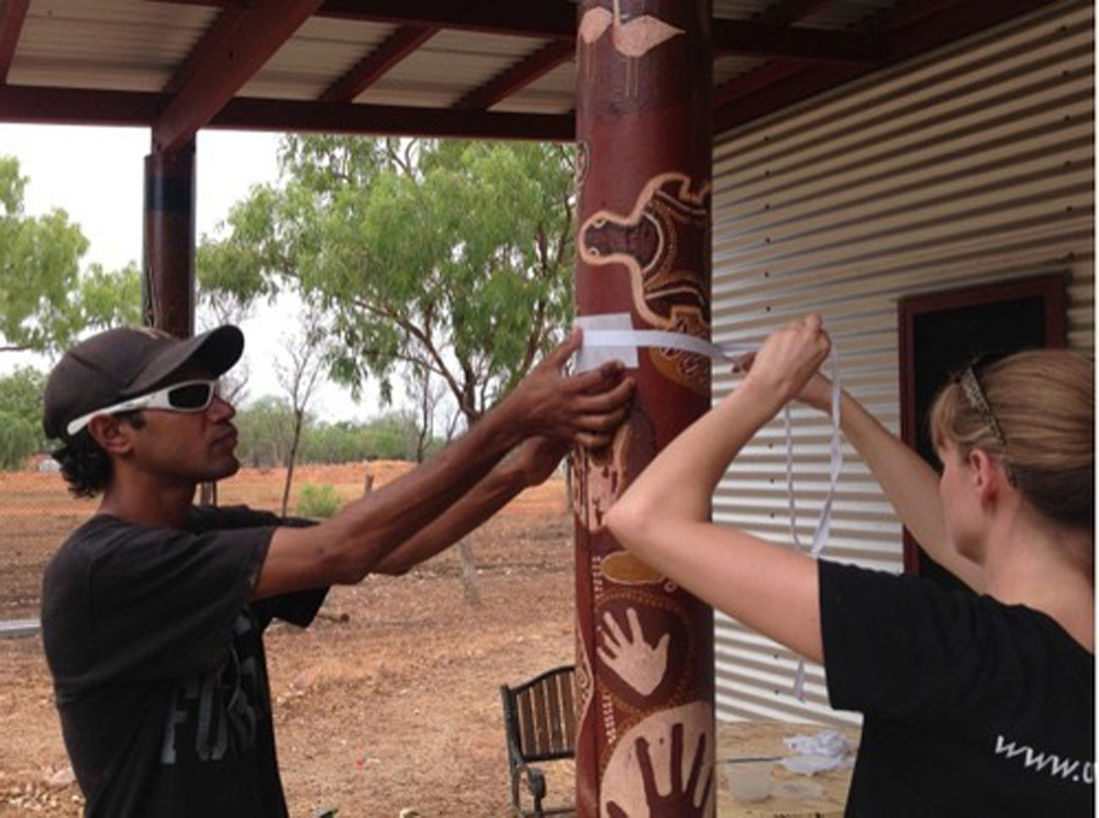 Sophie and Kenny, an arts centre employee, work together to re-adhere delaminating paint flakes to the outdoor wooden pole / Photograph by Jenny O'Connell