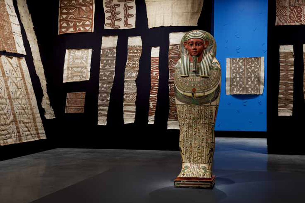 MONA's 2012 exhibition  Theatre of the World , which demonstrated a unique potential for collaboration by displaying over eighty Indigenous tapas from the TMAG collection alongside an Egyptian sarcophagus
