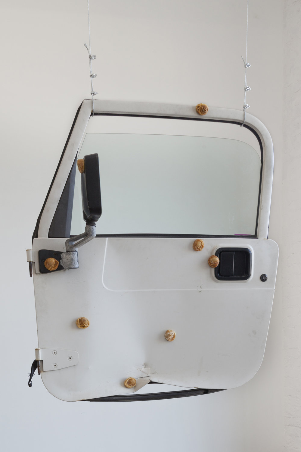 "Catalina Ouyang, ""when it dies its head will turn toward the hill where it was born,"" 2018 car door, dehydrated raw eggs, epoxy clay, incense, cable 37h x 41w x 12d in"