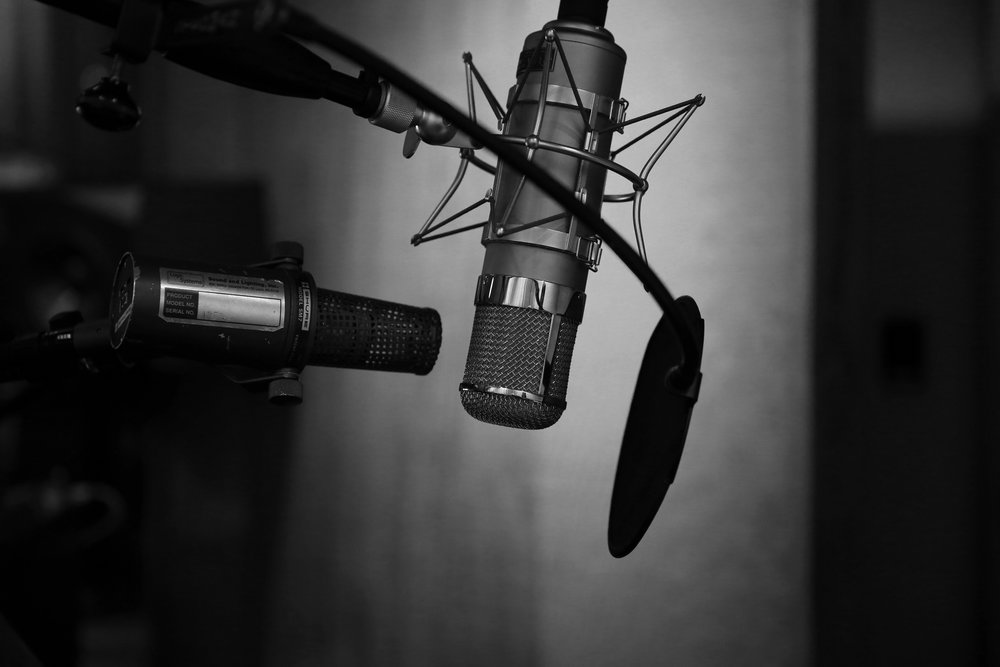Photo by  neil godding  on  Unsplash   Photo Description: A black and white photo of two mounted microphones and a windscreen. the mics are in focus and show great detail, while the background is unfocused, providing the perfect shades of gray and black.