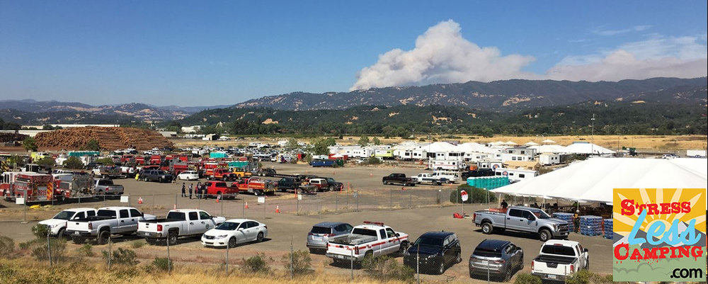 A shot of the fire camp with the Mendocino Complex fire in the background. In the mid-ground are the sea of RVs from participants who are using them to call home during this work.