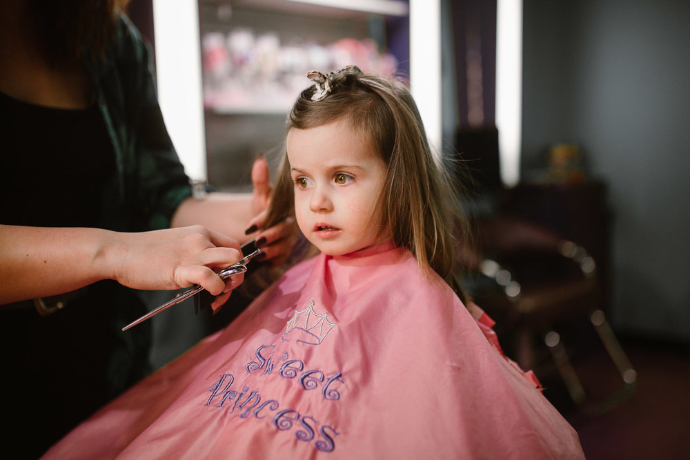Toddler in a pink cape getting her first haircut at Sweet and Sassy