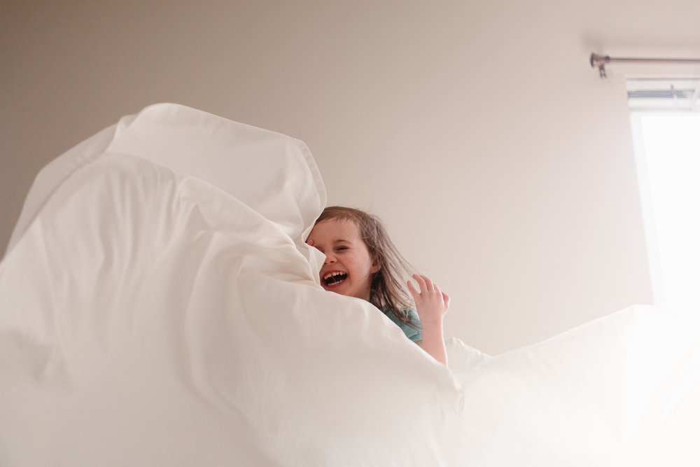 Toddler girl laughing and jumping on the bed with the sheets flying around her
