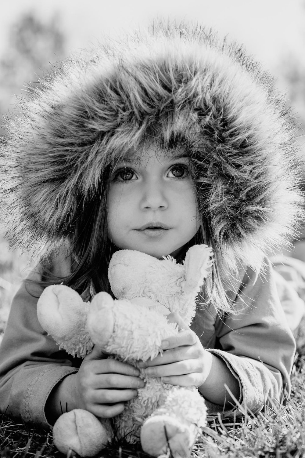 Black and white portrait of a toddler wearing a fur hood holding a stuffed lamb.