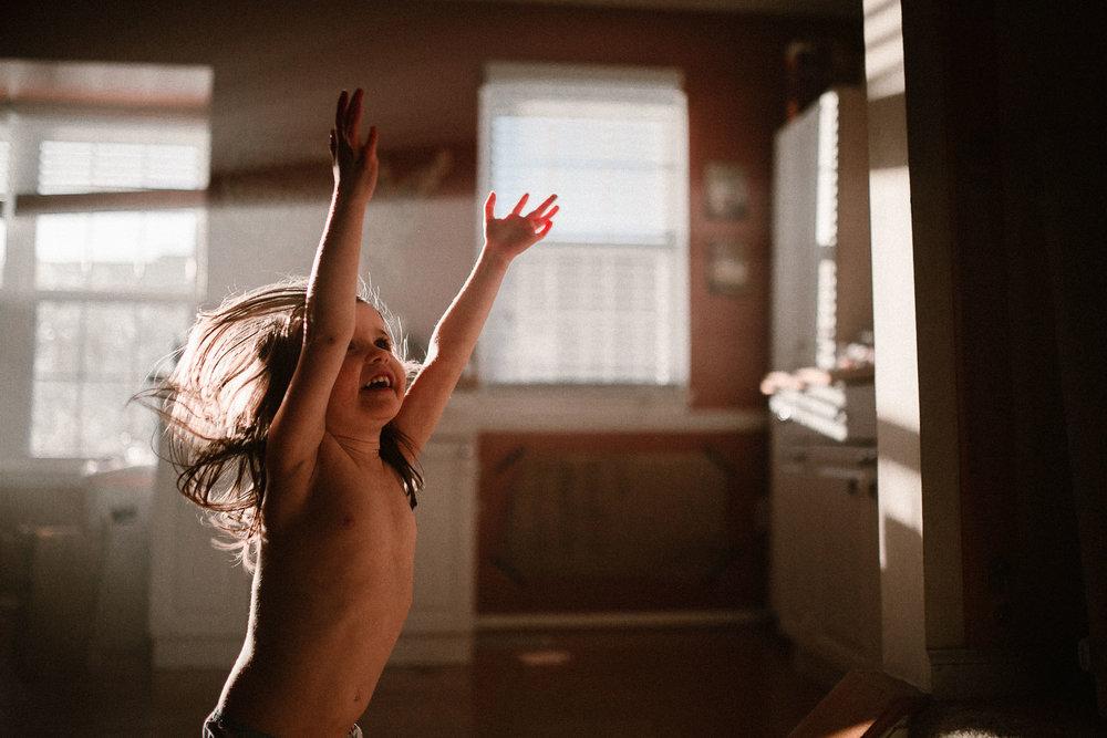 Toddler jumping and dancing in a room filled with light beams