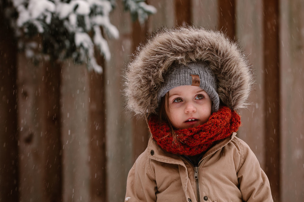Toddler bundled in a brown coat and orange scarf playing in the snow