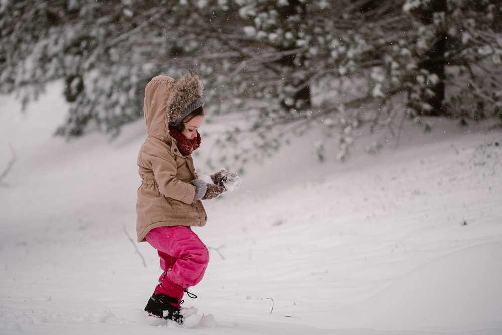 Toddler in pink pants and brown coat walks through the snow while making a snowball