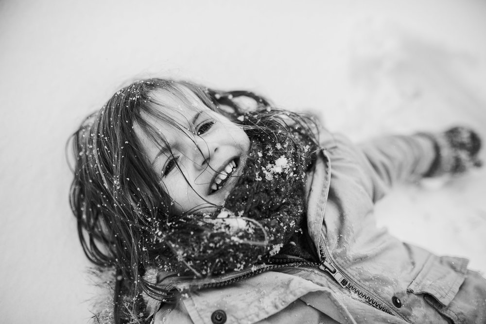 Black and white portrait of a toddler lying in the snow and makes a snow angel