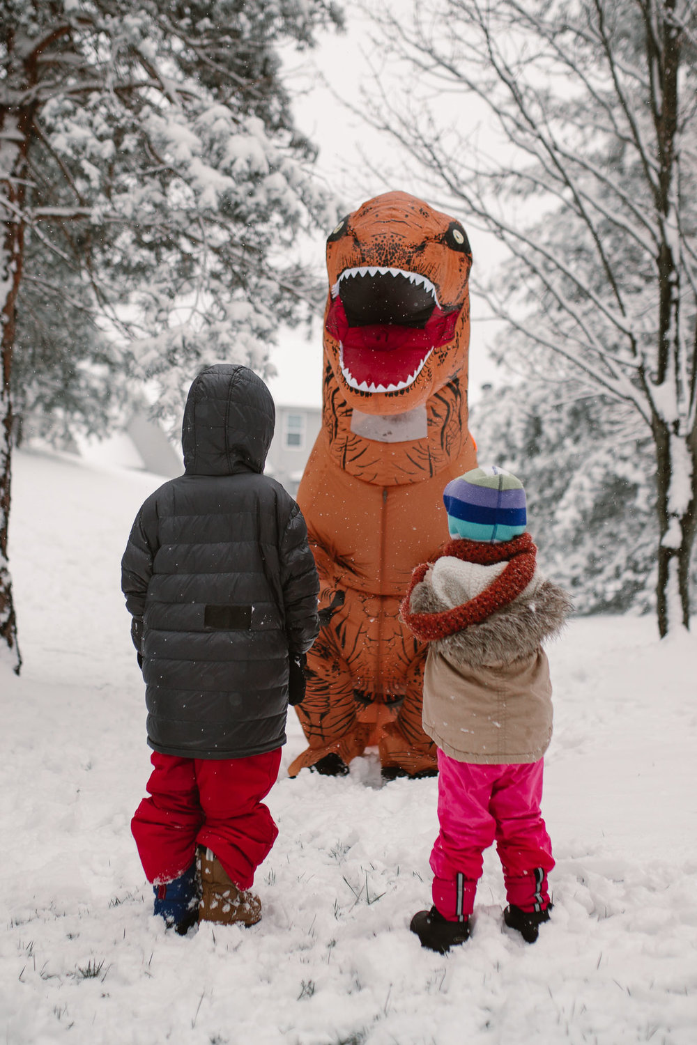 Two children stare up at a big orange dinosaur as they play outside in the snow