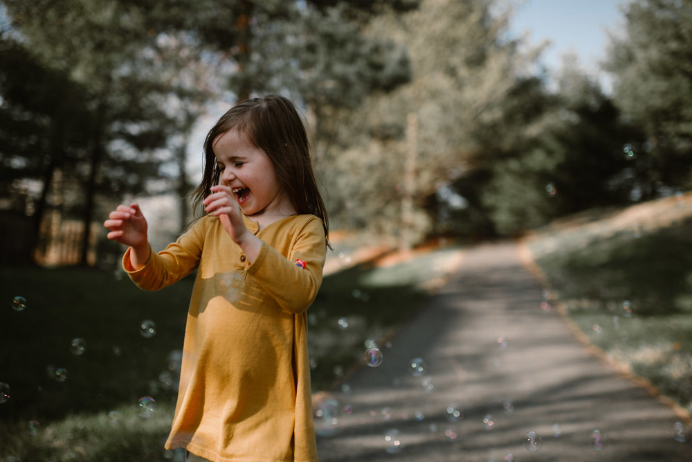 Girl in a yellow dress laughs as she runs through a stream of bubbles