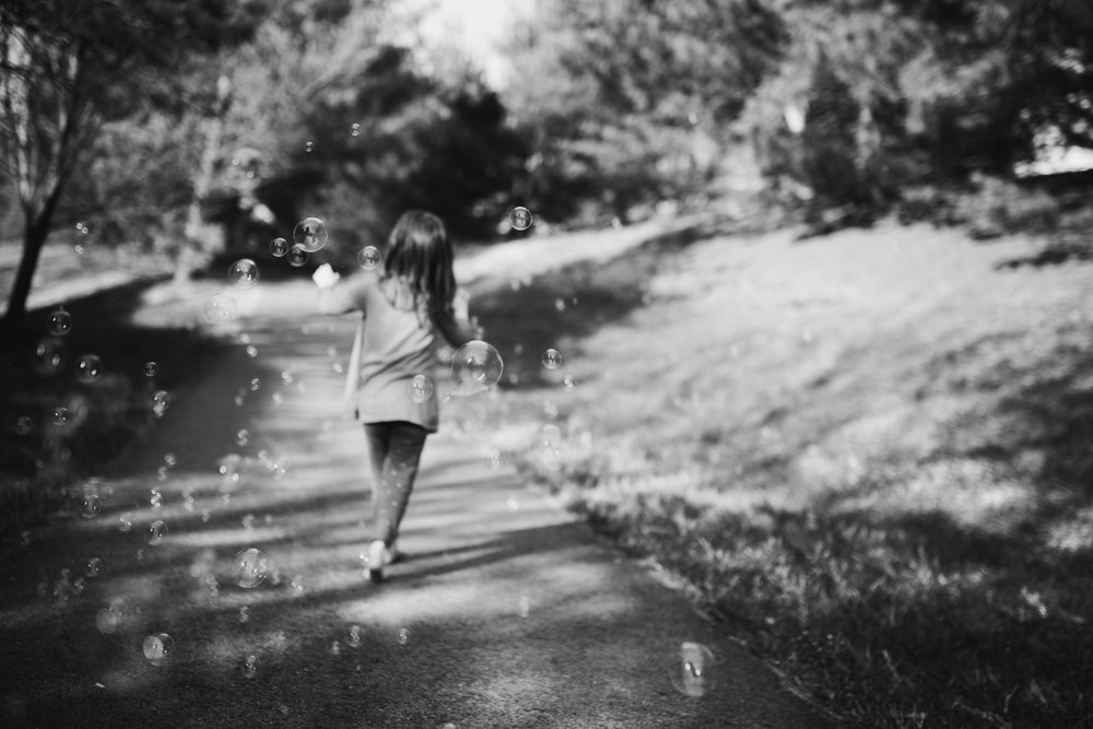 Black and white portrait of a toddler girl walking through a stream of bubbles