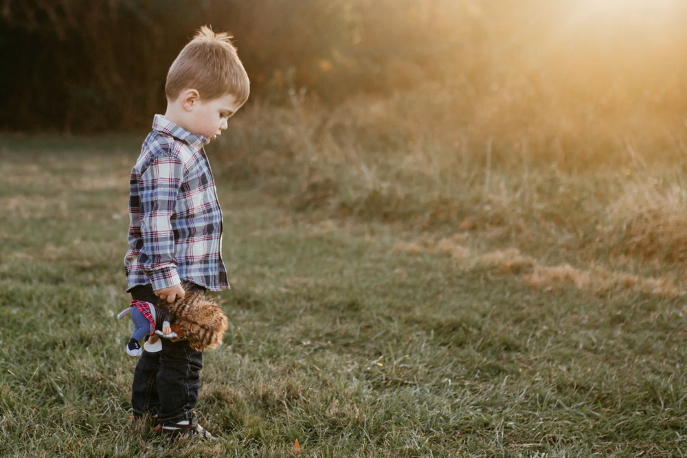 Boy holding his favorite stuffed animal in a field at sunset; Claude Moore Park, Sterling, VA