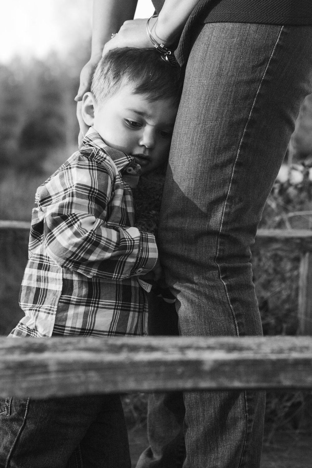 Black and white; boy hugging his mom's legs as she comforts him; Claude Moore Park, Sterling, VA