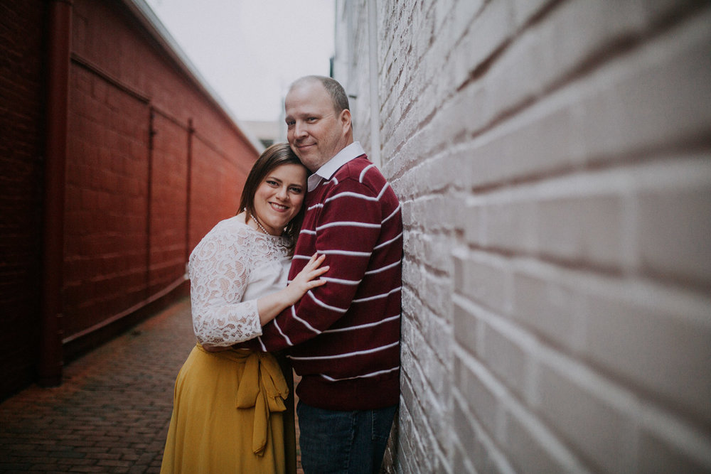 Man leans against a wall and his wife hugs him;  Downtown Leesburg Virigina