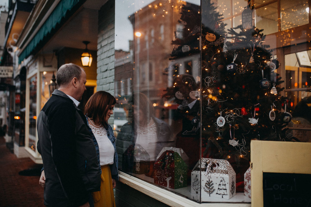 Couple is reflected in shop window as they admire the Christmas decorations in  Downtown Leesburg Virigina