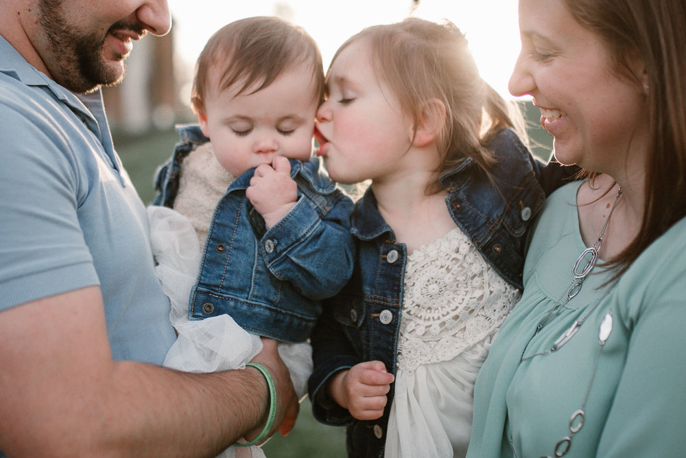 Parents holding their two daughters as the big sister tries to give her little sister a kiss at Ida Lee Park in Leesburg, VA