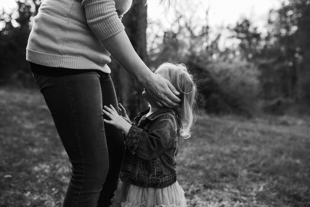 Black and white; mother leans down with her hands on her daughter's cheeks in order to comfort her at Red Rock Overlook in Leesburg, VA